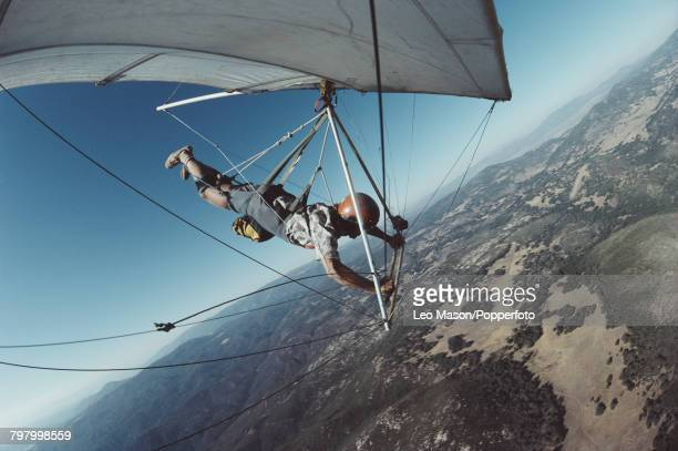 View of a pilot suspended under a hang glider as it flies over the Black Mountains range near Death Valley in California in 1981