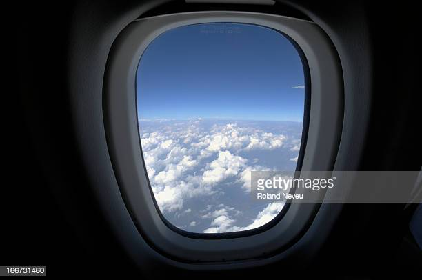 View of a plane window looking over cloudy sky.