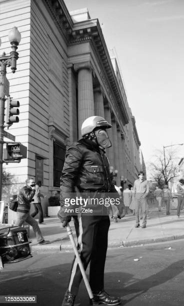 View of a police officer in a helmet and gas mask, a baton in his hand, as he walks on Pennsylvania Avenue NW at the intersection with 15th Street...