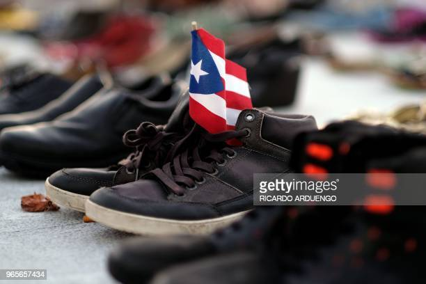 View of a Puerto Rican flag placed on a pair of shoes among hundreds displayed in memory of those killed by Hurricane Maria in front of the Puerto...