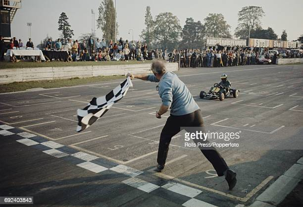 View of a race official waving a checkered flag to signal the end of competition as the winning driver crosses the finish line in a Gokart race at...