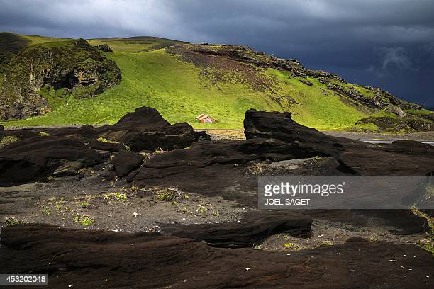 View of a red little house on a lava field near Vik south of Iceland on July 7 2014 AFP PHOTO / JOEL SAGET