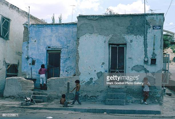View of a residential area with a blue, adobe house and several children at play, Juarez, Mexico, late 1980s.