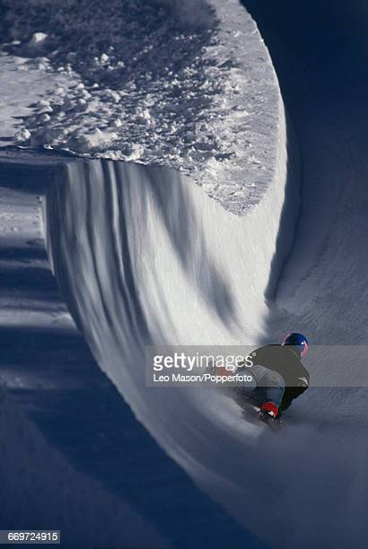 View of a rider on an ice skeleton racing toboggan flying down the Cresta Run style toboggan track constructed on a mountain in the town of St Moritz...