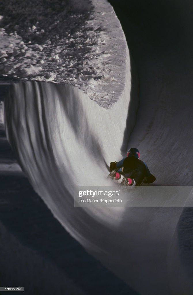 View of a rider on an ice skeleton racing toboggan flying down the Cresta Run style toboggan track constructed on a mountain in the town of St Moritz in Switzerland circa 1990.