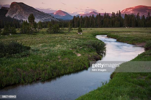 View of a river running through grassland in a valley in California.