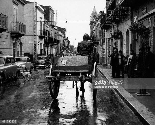 View of a road of the village of San Cipirello in the province of Palermo a man driving a cart transporting grains is being greeted by a group of men...