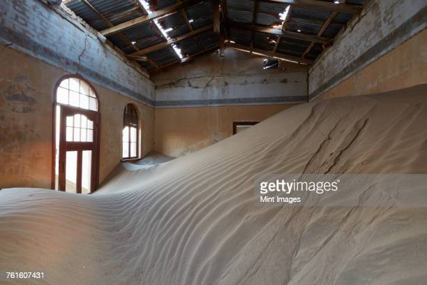 A view of a room in a derelict building full of sand.
