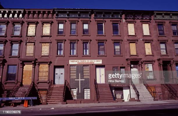 View of a row of abandoned and boarded up buildings including the Tabernacle Church of God in Christ on West 126th Street Harlem New York New York...