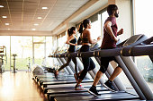 View of a row of treadmills in a gym with people.
