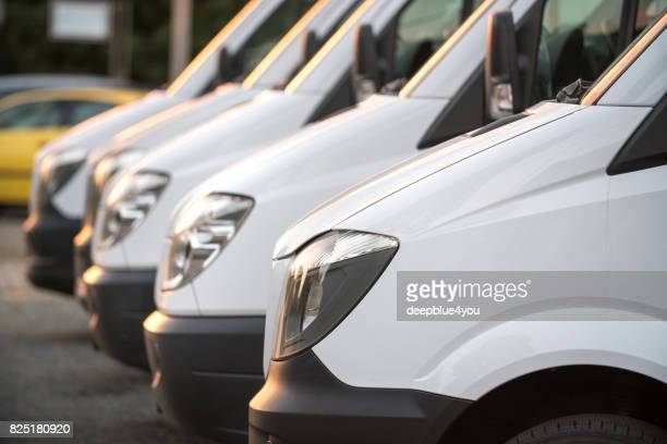 view of a row white van vehicles at a public place from a car dealer - out of frame stock pictures, royalty-free photos & images