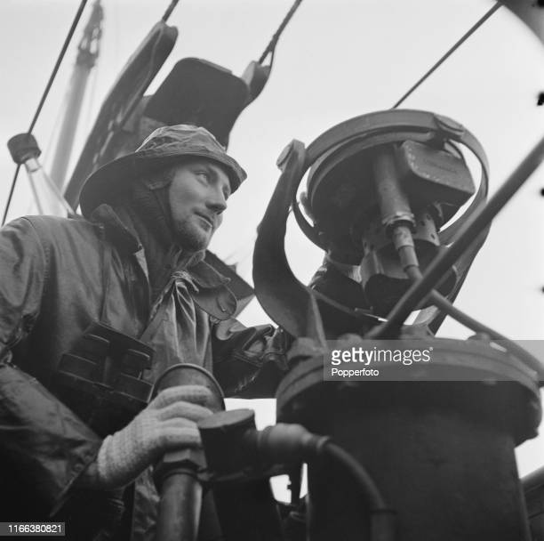 View of a Royal Navy officer taking a bearing on the bridge of a British submarine prior to going back on patrol during operations in the North Sea...