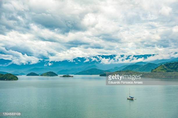 view of a sailboat with islands, sea and mountains on the background, in the archipelago region of angra, against an overcast sky - islands in the sky stock pictures, royalty-free photos & images