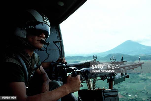 View of a Salvadoran soldier a gunner on a helicopter during a patrol near the Guazapa volcano central El Salvador September 1 1984 At the time the...