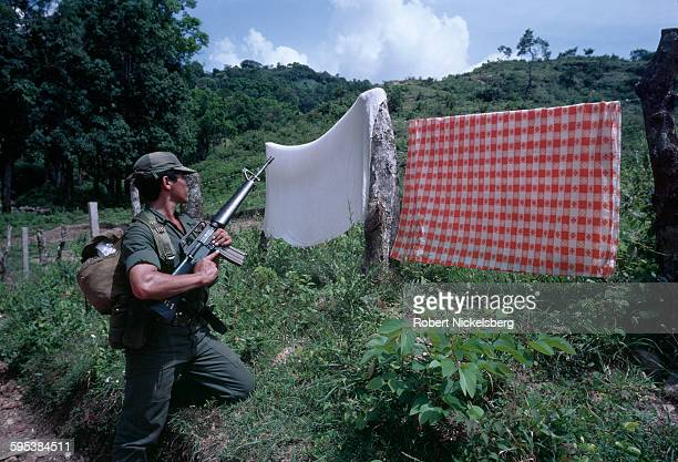 View of a Salvadoran soldier kneels behind a pair of blankets hung over a barbedwire fence in the Chalatenango province El Salvador October 1 1981 At...