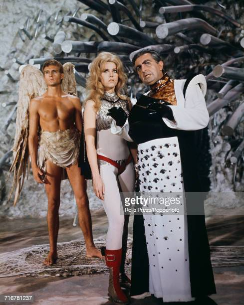 View of a scene from the science fiction film Barbarella with Irish actor Milo O'Shea in character as Durand Durand directing Jane Fonda as...