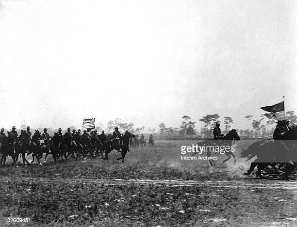 View of a scene in the Spanish American War, where the color bearers of the US Third Cavalry lead the attack, 1898. US Army photo.