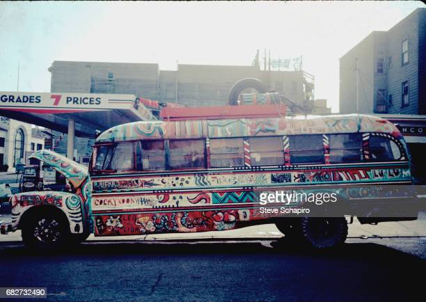 View of a school bus painted in psychedelic patterns in front of a gas station in the HaightAshbury neighborhood San Francisco California 1967