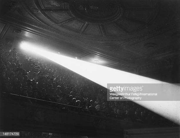 View of a shaft of light from the film projector as it shines over the heads of cinema patrons seated in a theater balcony during a Saturday...
