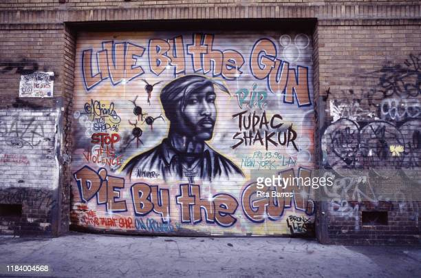View of a sidewalk mural, 'Live By the Gun, Die By the Gun' with an image of rapper Tupac Shakur, New York, New York, 1997.
