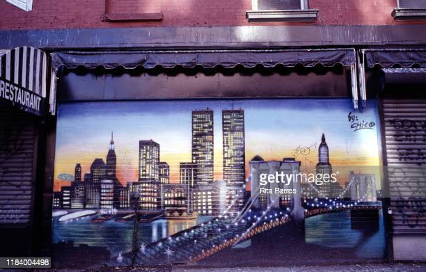 View of a sidewalk mural of the New York City skyline , New York, New York, 1993. It features the Brooklyn Bridge in the foreground and the twin...