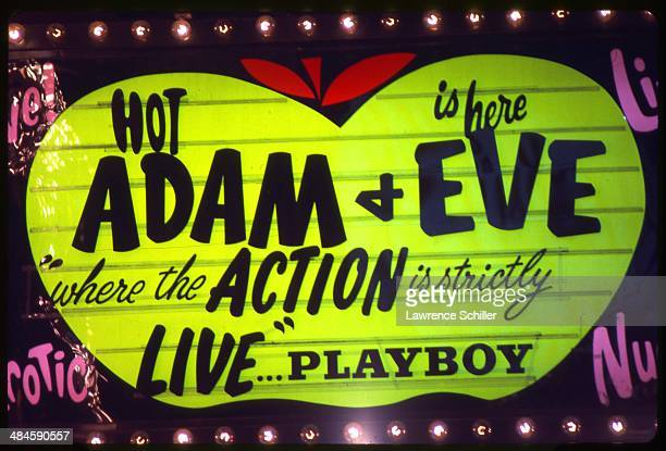 View of a sign on a pornography theatre which advertises 'Hot is Here Adam Eve Where the Action is Strictly Live' San Francisco California 1976