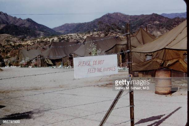 View of a sign that reads 'Please Do Not Feed the Animals' on a barbed wire fence around the officers' compound at the 8063rd MASH South Korea...