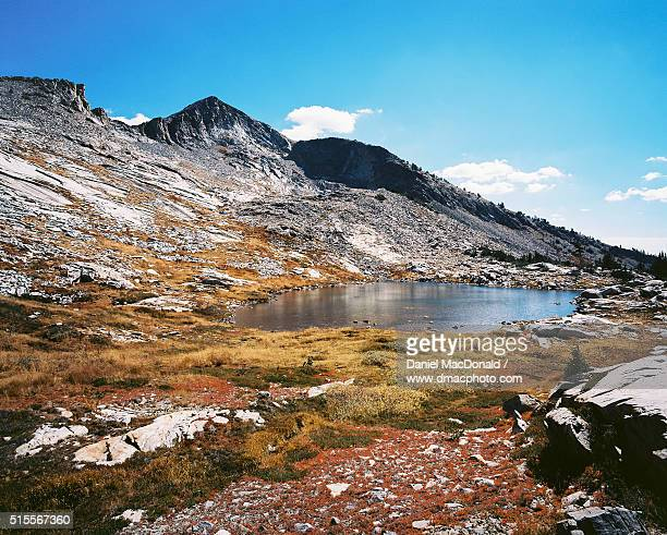 View of a small alpine lake in autumn with Pyramid Peak in the background