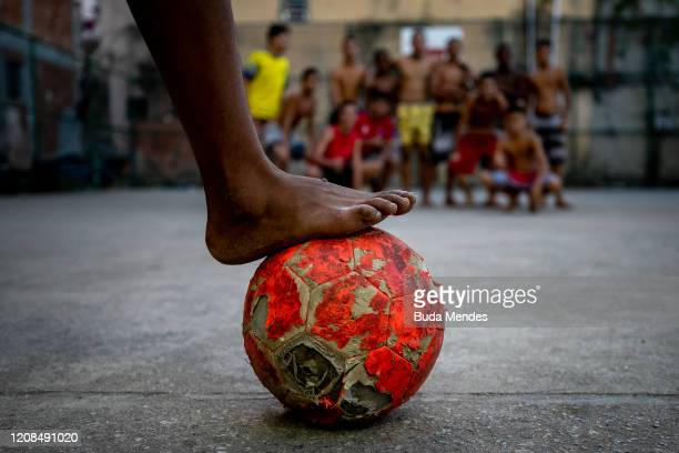 A view of a soccer ball and a group of boys in the distance at Piscinao de Ramos community amidst the coronavirus pandemic on March 28 2020 in Rio de...