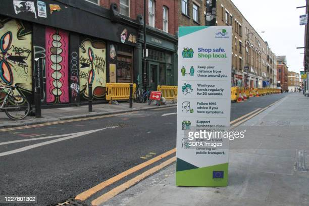 View of a social distancing information sign on Brick Lane. The Government has made it mandatory to wear face coverings in all public transport,...