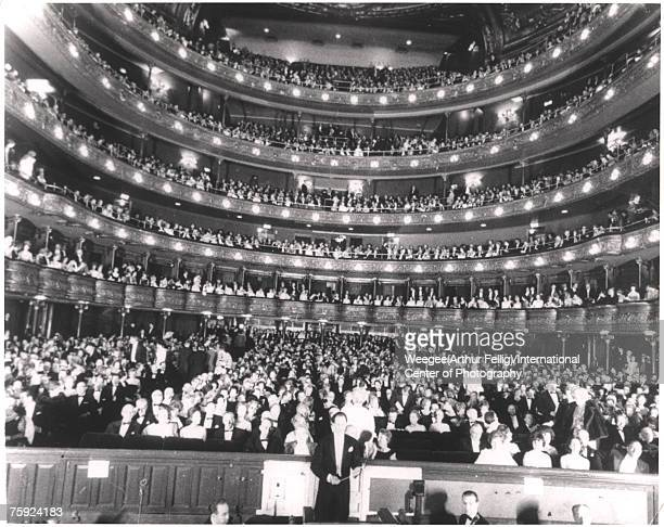 View of a sold out audience in their seats at the Metropolitan Opera House, as seen from the stage, New York, New York, 1940s. The conductor can be...