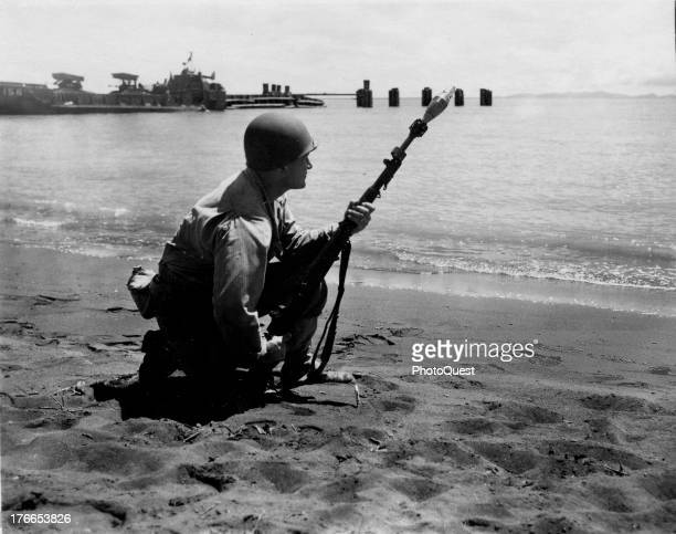 View of a soldier kneeling on the beach and demonstrating and explaining the use of various types of firearms and equipment on Guadalcanal May 8 1944