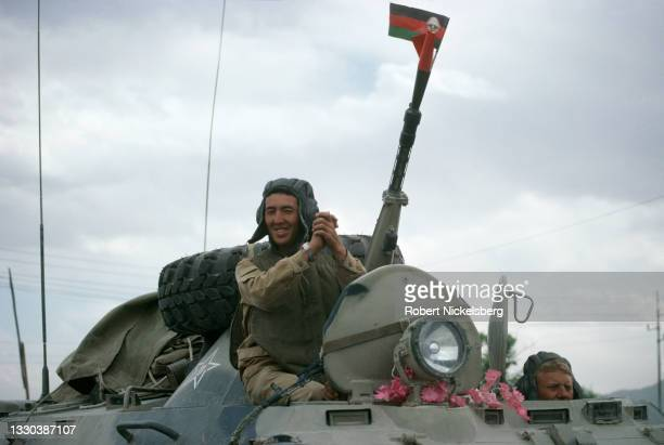 View of a Soviet army soldier, clasping his hands, as he rides an armored vehicle during the final Soviet troop withdrawal ceremony, Kabul,...