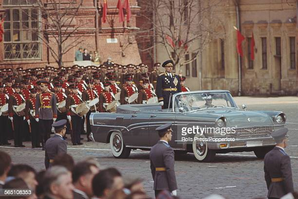 View of a Soviet general standing to attention in the rear passenger area of a ZiL111V convertible limousine making up part of a May Day parade in...