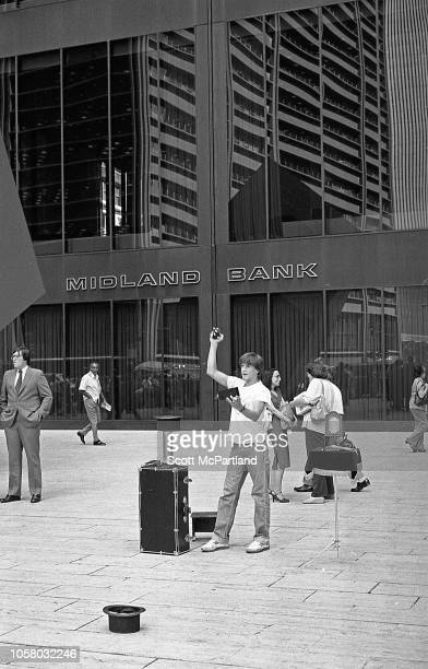 View of a street magician performs in front of the Marine Midland Bank building in lower Manhattan New York New York September 1980 Reflected in the...