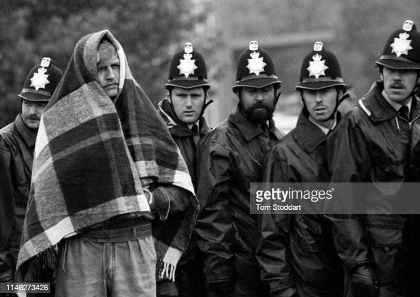 View of a striking miner a blanket over his head against the rain stands in front of a line of police officers near the Orgreave coking plant...