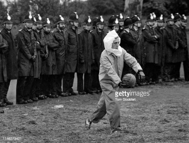 View of a striking miner as he kicks a soccer ball in front of a line of police officers near the Orgreave coking plant Orgreave Yorkshire England...
