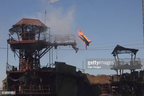 View of a stunt performer on fire and 'falling' from a platform during Universal Studios Hollywood's 'Waterworld A Live Sea War Spectacular' show Los...