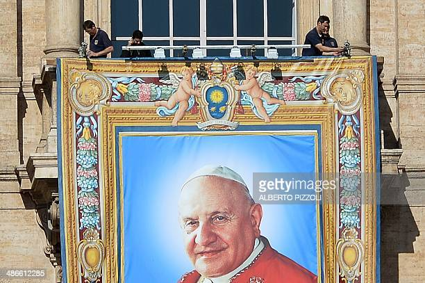 View of a tapestry showing a portrait of late Pope John XXIII hanged on the balconies of St Peter's basilica on April 25 2014 in Vatican two days...
