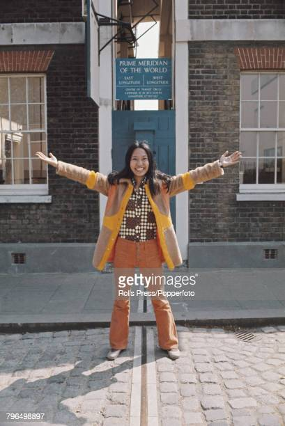 View of a tourist visitor standing bestriding a metal strip marking the prime meridian longitude line that divides the Earth in to two hemispheres...