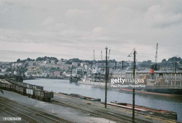 View of a tramp steamer moored at the Floating Harbour, part of the Port of Bristol, in the city of Bristol in England circa 1960. Goods trucks are...