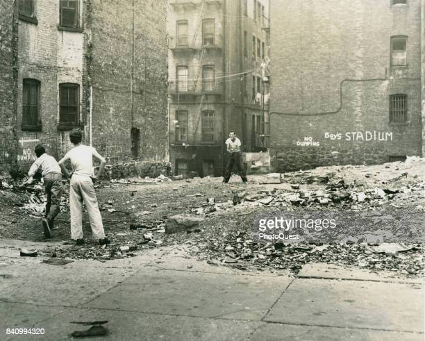 View of a trio of boys as they playing catch in a rubblestrewn vacant lot labelled 'Boy's Stadium' New York New York August 30 1954