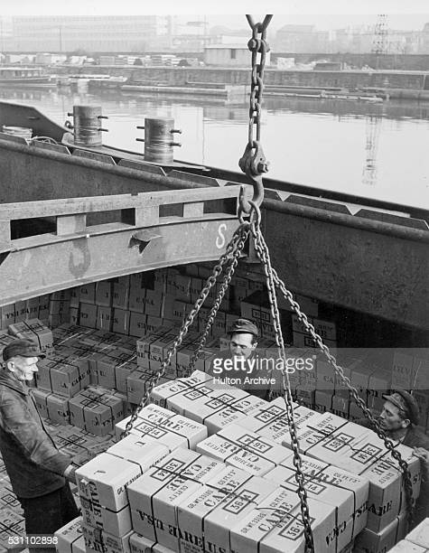 View of a trio of stevedores as they unload CARE packages from a ship Germany 1940s or 1950s CARE was a humanitarian agency its acronym later changed...