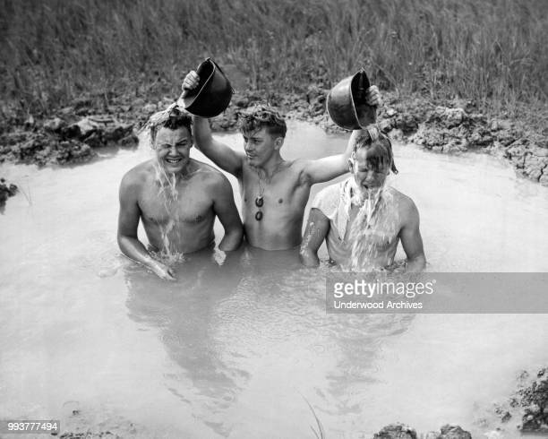 View of a trio of unidentified American soldiers, tankmen of the Sixth Marine Division, as they bath in a shell hole, Okinawa, Japan, June 1945.
