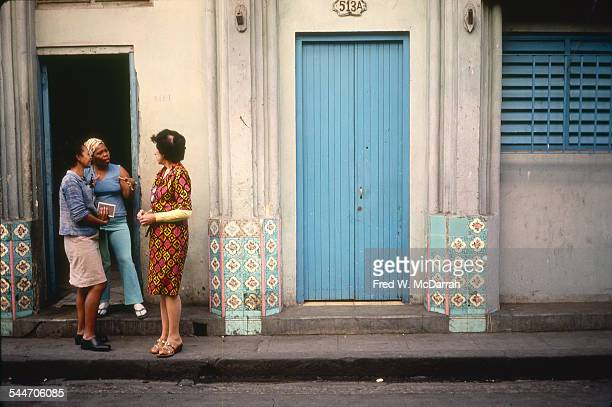 View of a trio of women as they stand and talk in a doorway decorated with colorful tiles Old Havana Cuba January 1983