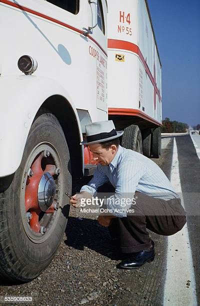 A view of a truck driver checks the pressure in his tires as he drives a Mack Truck for Cooper Jarrett Motor Freight Lines in Illinois
