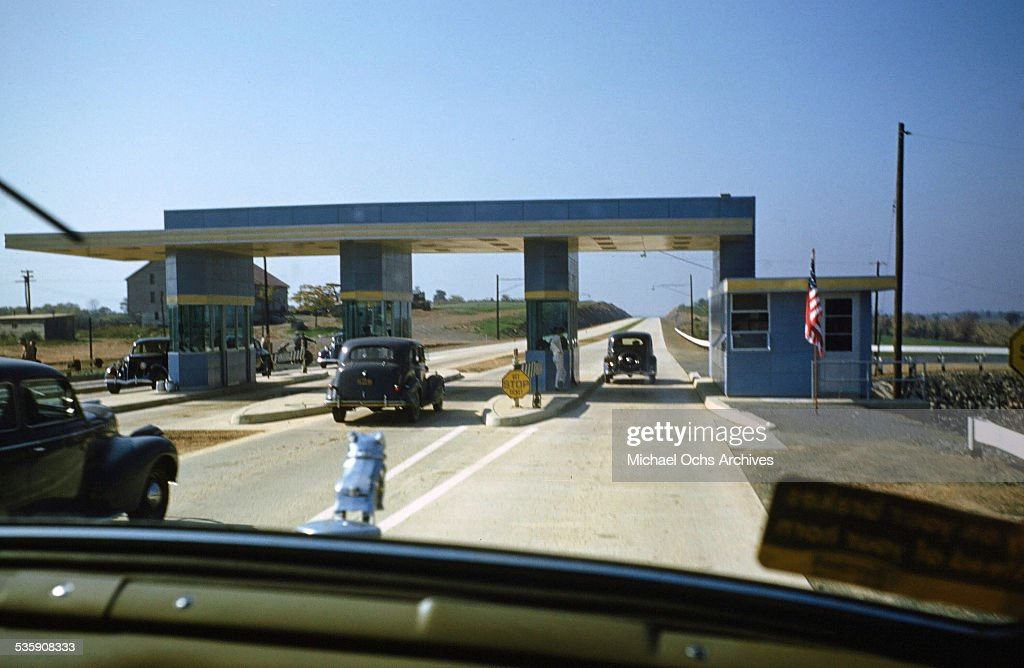 A view of a truck driver, driving a Mack Truck through a toll for Cooper Jarrett Motor Freight Lines in Illinois.