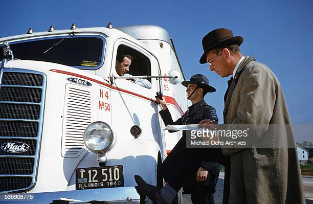 A view of a truck driver is stopped by a highway patrol officer as he drives a Mack Truck for Cooper Jarrett Motor Freight Lines in Illinois
