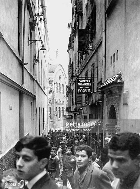 View of a typical alleyway in the casbah in Algiers full of children playing and running in the middle of the crowd