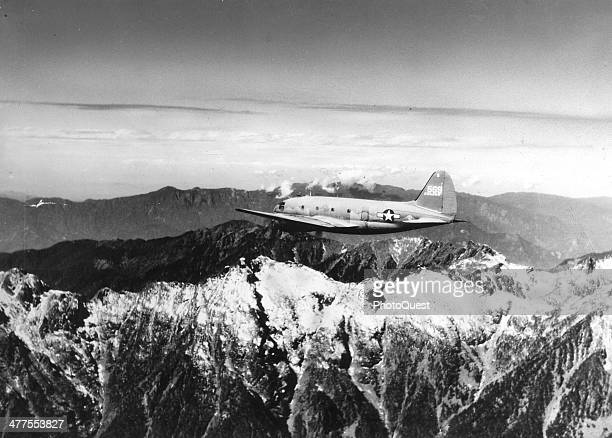 View of a US Army Air Transport Command cargo plane as it flies over the snowcapped towering mountains of the Himalayas along the borders of India...